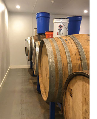 55-gallon wine barrels hold fermenting beer at Barreled Souls. The buckets above the barrels act as yeast harvesting devices and airlocks. Photo by Matthew Brown