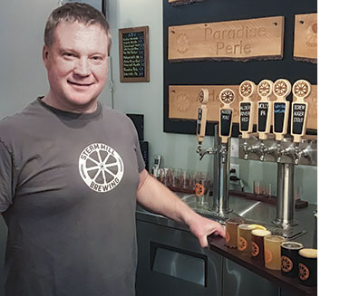 Scott Fraser pours a flight of brews at Steam Mill Brewing. Photo: Carey Kish