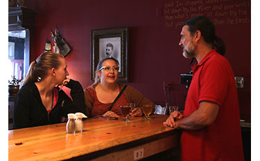 Lubec Brewing Co. owner Gale White chats with customers Emily O'Neil and Tara Legris.