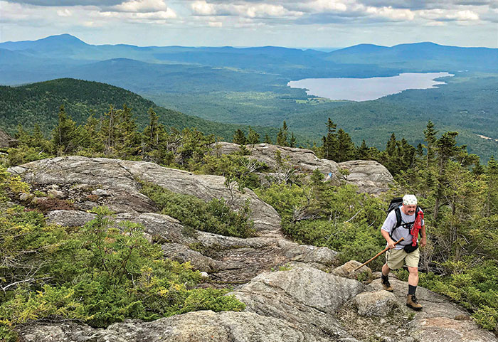 A hiker scrambles over the upper ledges on Parker Ridge Trail, Tumbledown Mountain. Photo by Carey Kish.