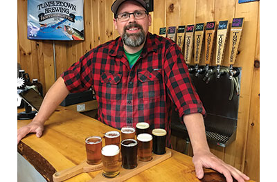 Dave Allen happily serves up a couple of great flights of brew at Tumbledown Brewing in Farmington. Photo by Carey Kish.
